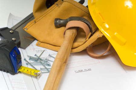 cinta de medir: Elementos utilizados por un trabajador de la construcci�n incluyendo un cintur�n de cuero herramienta, un martillo, una cinta m�trica, herramientas, plantas y un casco amarillo