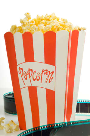 entertainment industry: A box of popcorn with a stip of 35mm film on a white background, symbols of the entertainment industry