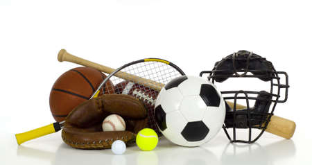 A variety of sports gear on a white background including tennis racket and ball, a soocer or football, an american football, a baseball bat, glove and catchers mask and a basketball with copy space