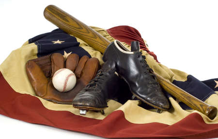 mitt: Vintage, antique baseball gear on vintage American flag bunting, inlcuding a baseball mitt or glove, baseball shoes or cleats, a baseball bat and a baseball. sports background