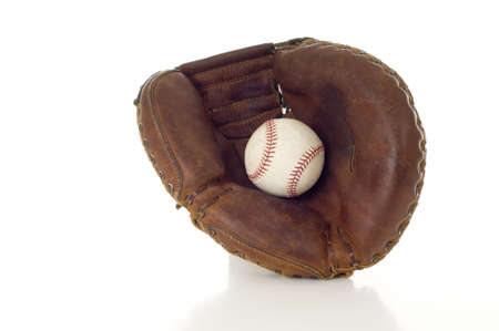 catchers mitt: A brown leather baseball mitt with a white leather baseball on a white background with copy space