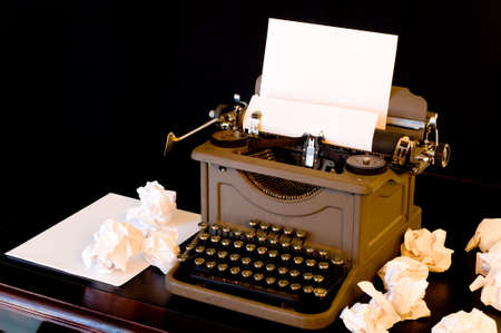 A vaintage typewriter with several wadded up pieces of paper arranged around it.  symbol of writers block or difficulty with creativity Stock Photo