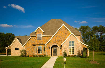 real esate: A beautiful two story home with a green lawn and a beutiful blue sky.  Real esate concept Stock Photo