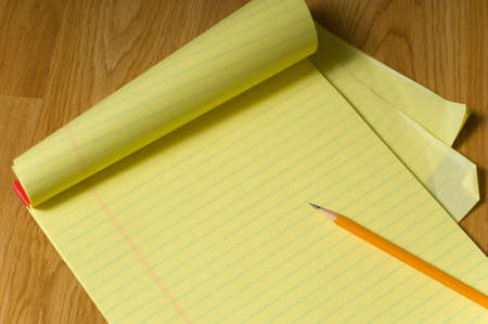 A blank, yellow legal pad on a brown wooden desk or floor with a writing pencil on the edge, add your own copy photo