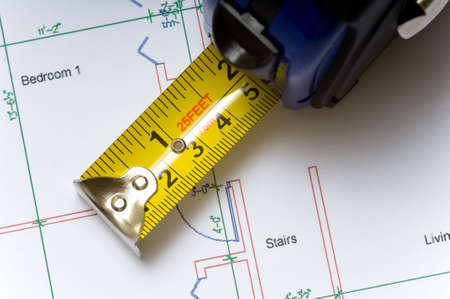 real esate: A tape measure slightly open lying on top of a house floor plan, construction industry or real esate