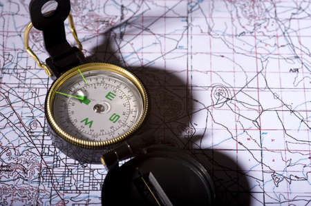 A compass lying on top of a topographical map