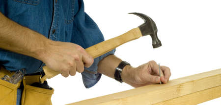 handy: A construction worker or handy man driving a nail with a hammer in  two 2 x 4s