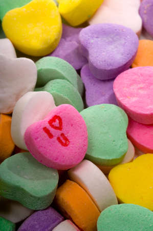 A stack of candy conversation hearts with one turned up with the words I love you visible, focus is on the printed heart  Banco de Imagens