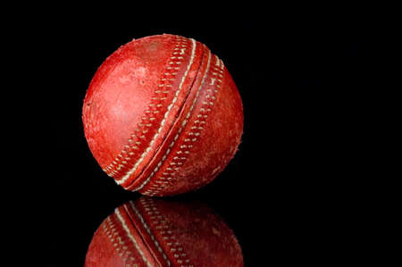 scuff: Red, scuffed Cricket ball on black background with reflection