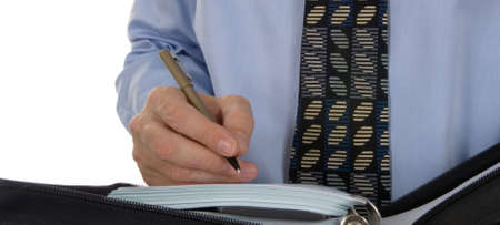 scheduling: Business man writing, scheduling in paper organizer, calendar