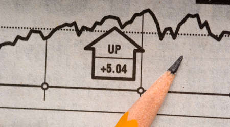 A pencil lying on top of a newspaper stock chart signaling an increase in price or a rising market Imagens
