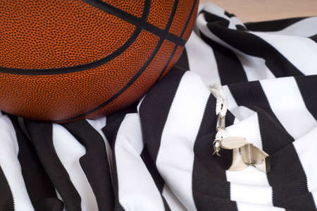 whistles: A basketball referees items including a ball, a striped jersey and a whistle Stock Photo