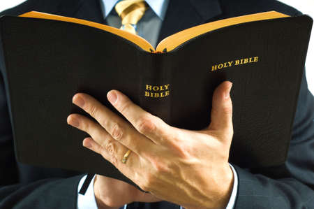 A man is business suit reading the Bible could be a preacher