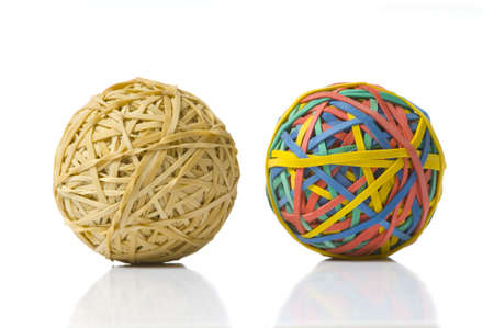 opposites: Two rubberband balls, illustration of opposites, or being different and refusing to be ordinary or boring Stock Photo