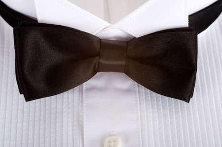 Een achtergrond bestaande uit een smoking shirt met een zwarte zijden stropdas met kopie ruimte, formele kleding voor bruiloft of ober of service personeel
