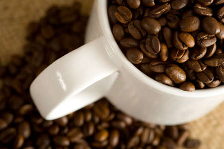 A white cup full of roasted coffee beans on a burlap coffee bean bag.  Background with copy space Stock Photo - 3038348