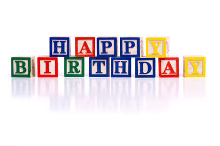 childs birthday party: The words happy birthday spelled out in wooded block on a white background with copy space