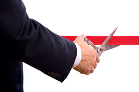 A business man wearing a blue suit cutting a red ribbon with a pair of shiny silver scissors.  Grand opening ceremony or event photo