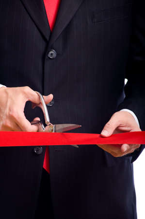 shiny suit: A business man wearing a blue suit cutting a red ribbon with a pair of shiny silver scissors.  Grand opening ceremony or event