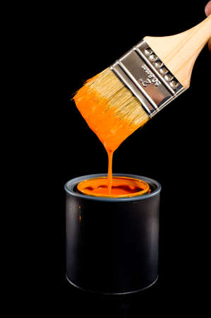 Colorful can of orange paint with a paint brush with dripping paint with space for copy etc. 스톡 콘텐츠