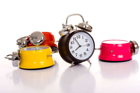 Several brightly colored traditional alarm clocks thrown on a white background