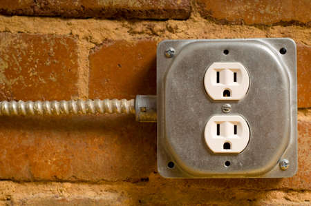 Industrial electrical outlet on a red brick wall, concept of power or connectivity etc.