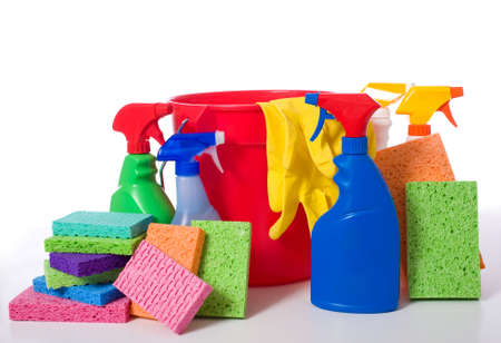 a variety of cleaning supplies and chemicals on a white background, including spray bottles, gloves, sponges, rags, and a bucket photo