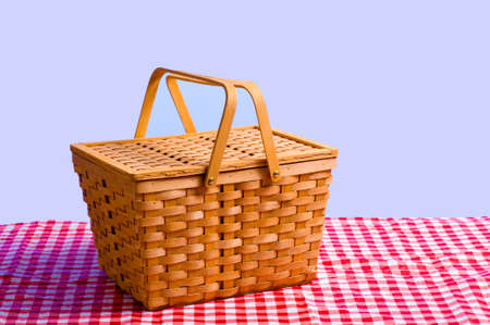 a brown wicker antique picnic basket on a gingham tablecloth in front of a blue sky