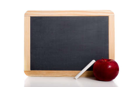 A blank school chalkboard or slate on a white background with an apple and a piece of white chalk, with copy space