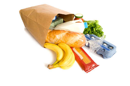 groceries: A brown paper bag full of groceries on a white background, with bread, milk, eggs, pasta, lettuce and bananas.  with copy space Stock Photo