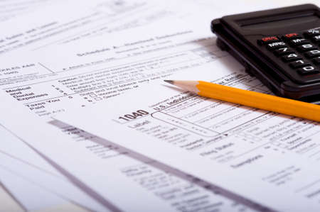 compute: Tax prepaation items including a pencil, calculator and tax forms Stock Photo