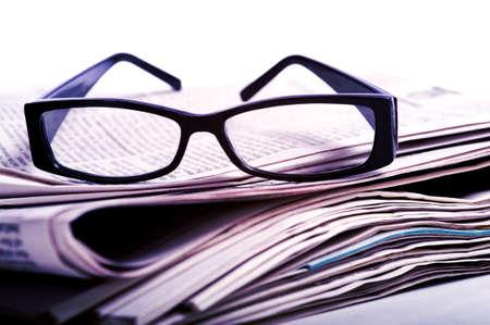 gafas de lectura: Un par de gafas de lectura negro en la parte superior de una pila de peri�dicos sobre un fondo blanco