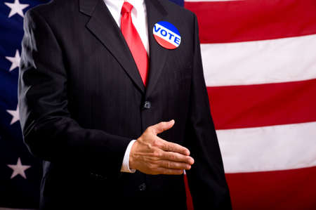 then: A politician in a blue suit and red necktie extending his hand to be shaken.  Standing in front of an American flag.  shallow depth of fiield focus is on hand and then falls off
