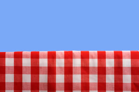 A summertime or springtime picnic background with a gingham tablecoth and a blue sky with ample copy space Stock Photo - 3875051