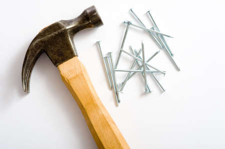 handled: A wooden handled hammper and several nails lying on top of a white background
