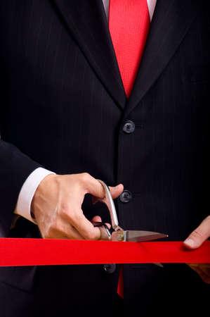 taglio del nastro: Un uomo d'affari che indossa tuta blu taglio un nastro rosso con un paio di forbici d'argento lucido. Grande cerimonia di apertura o di un evento
