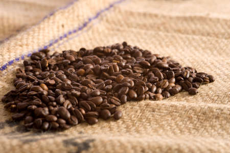 Roasted Coffee beans lying on top of a brown burlap coffee bean transportation bag Stok Fotoğraf