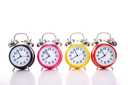 A row of colorful alarm clocks on a white background