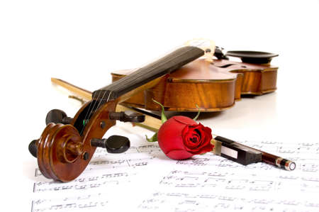 A violin a rose and sheet music on a white background, focus is on the peg head of the violin and the rose photo