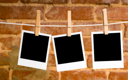 instant transfer pictures on a rope with clothespins, in front of a brick wall