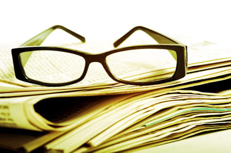 A pair of black reading glasses on top of a stack of newspapers on a white background photo