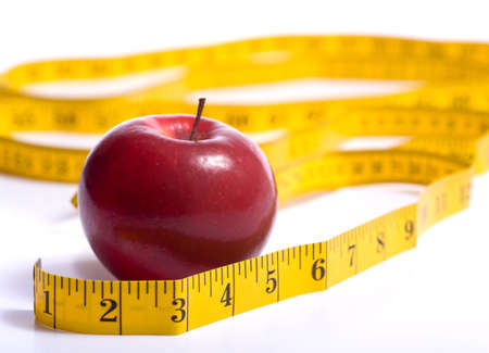 A red apple and a yellow tape meausure on a white background.  Dieting or healthy eating concept.   photo