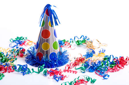 excite: A brightly colored birthday hat and streamers on a white background with copy space