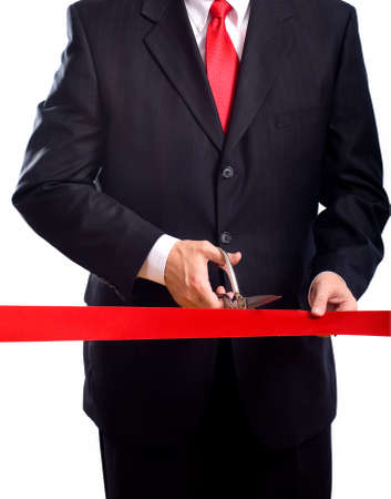 A business man wearing a blue suit cutting a red ribbon with a pair of shiny silver scissors.  Grand opening ceremony or event Stock Photo - 4722751