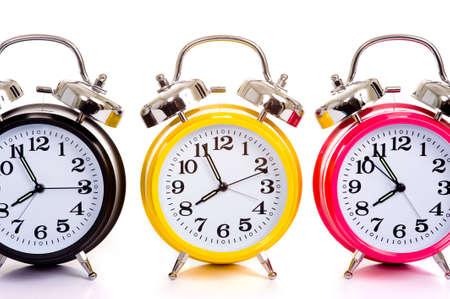 despertador: un grupo de relojes multicolores sobre fondo blanco, con copia espacio