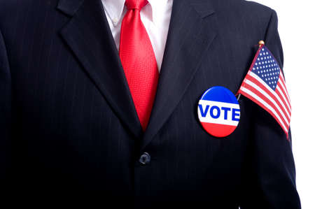 blue button: A man wearing a blue business suit and tie with a vote button and US flag.  Election day background or concept