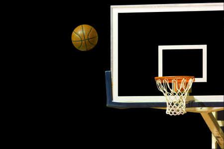 A shot basketball flying toward a basketball goal on a black background