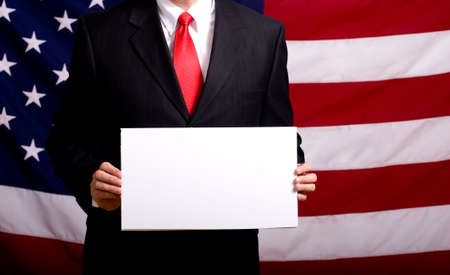 elected: A politician or business man in a suit holding a blank white sign in front of the American Flag