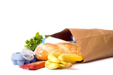 A brown paper bag full of groceries on a white background, with bread, milk, eggs, pasta, lettuce and bananas.  with copy space Archivio Fotografico