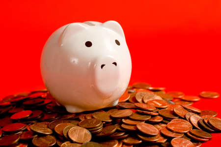 conept: A white piggy bank on a red background with lots of American pennies.  Financial crisis conept?   Stock Photo